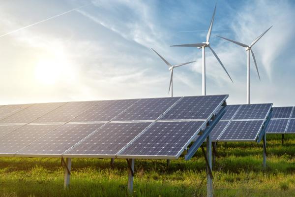 solar panels and wind generators under blue sky on sunset